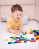 Pojken spelar med byggnadskvarter Arkivbild