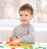Pojken spelar med byggnadskvarter Royaltyfria Bilder