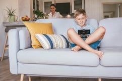 Pojken spelar med den elektroniska apparaten Hans moder förberedde något i det suddiga bakgrundsköket arkivbilder