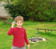 Pojken spelar med det pappers- flygplanet i trädgården Royaltyfri Foto