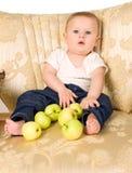 Pojken spelar med gröna äpplen royaltyfri foto