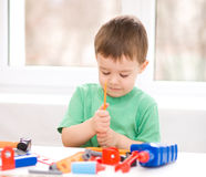 Pojken spelar med hjälpmedel Arkivbilder