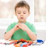 Pojken spelar med hjälpmedel Royaltyfria Foton