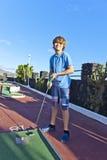 Pojken spelar minigolf Royaltyfri Bild