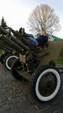 Pojken spelar på en stor tung kanon från tiderna av världskrig II på monumentet till sovjetiska soldater Fotografering för Bildbyråer
