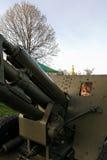 Pojken spelar på en stor tung kanon från tiderna av världskrig II på monumentet till sovjetiska soldater Arkivbild