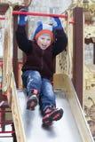 Pojken spelar på lekplatsen i vintern Arkivbild