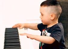 Pojken spelar pianot Royaltyfri Bild
