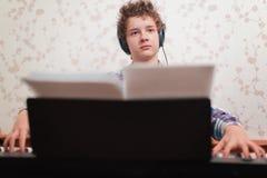 Pojken spelar pianot arkivfoton