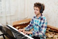 Pojken spelar pianot arkivbilder