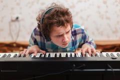 Pojken spelar pianot royaltyfria bilder