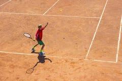 Pojken spelar tennis på den orange smutsdomstolen Domstol hårt Arkivfoton