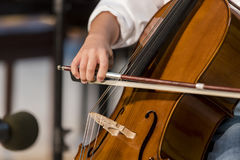 Pojken spelar violoncellen arkivbild