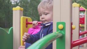 Pojken spelas på en lekplats i en parkera eller ett dagis Barnet är roligt att stoja lager videofilmer