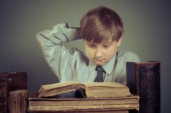 Pojken spenderar tid som läser gamla böcker Fotografering för Bildbyråer