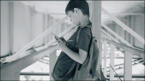 Pojken står i en kall metallkorridor Atmosfäriska skott Pojken ser smartphonen Det är under bron arkivfilmer
