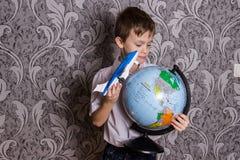 Pojken står med ett jordklot och ett flygplan i hans händer royaltyfri foto