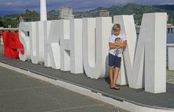 Pojken står på bokstäver med namn av staden Sukhumi arkivfoto