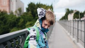 Pojken står på bron Vinden blåser i hans baksida fladdrande h?rwind Trevliga skott arkivfilmer