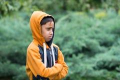 Pojken står på en gräsmatta och tänker Arkivbild
