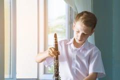 Pojken står vid fönstret med en svart klarinett Musicology, musikutbildning och utbildning royaltyfri fotografi
