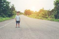 Pojken stod på gatan och att le på kameran med en fre Royaltyfria Bilder