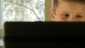 Pojken synar, medan arbeta på datorslut upp stock video