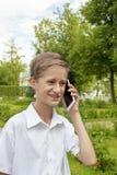 Pojken talar känslomässigt i parkera vid telefonen Fotografering för Bildbyråer