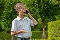Pojken talar känslomässigt i parkera vid telefonen royaltyfri bild