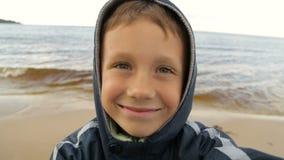 Pojken tar bilder av honom mot havet stock video
