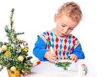 Pojken tecknar en julgran royaltyfria foton