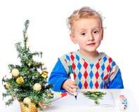 Pojken tecknar en julgran royaltyfria bilder
