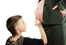 pojken tecknar framsidan hans gravida mom royaltyfri bild