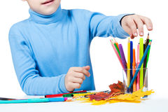 Pojken tecknar med blyertspennor royaltyfria foton