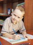 Pojken tecknar med blyertspennor i en anteckningsbok fotografering för bildbyråer