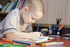 Pojken tecknar med färgrika blyertspennor i en bok royaltyfria bilder