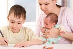 Pojken tecknar med hans moder och nyfött fotografering för bildbyråer