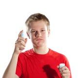 Pojken, tonåringen som besprutar doftdoft. Stående på en vit bakgrund Arkivfoto