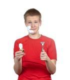 Pojken, tonåringen som den första gången försöker att ha en rakning och är förvirrad. Stående på en vit bakgrund Royaltyfria Bilder