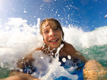 Pojken tycker om att rida vågorna med en surfingbräda arkivbilder