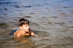 Pojken tycker om att simma i floden royaltyfria bilder