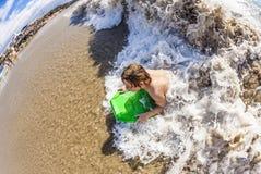 Pojken tycker om att surfa i vågorna Arkivbild