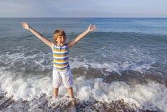 Pojken tycker om havet arkivfoto