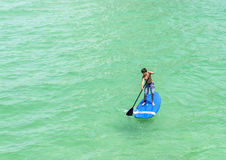 Pojken tycker om står upp skoveln som surfar i havet Arkivfoto