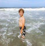 Pojken tycker om vågorna i havet Royaltyfria Bilder