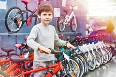 Pojken väljer cykeln i sportlager arkivfoto
