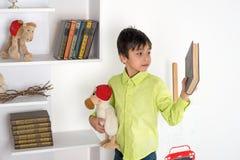 Pojken väljer mellan boken och en leksak Arkivfoto