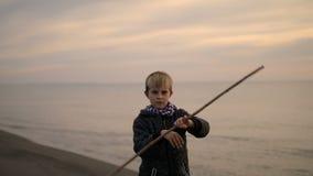 Pojken vänder pinnen i hans händer, medan stå på stranden på solnedgången stock video