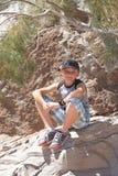 Pojken vilar på en halt i sommaren royaltyfria bilder