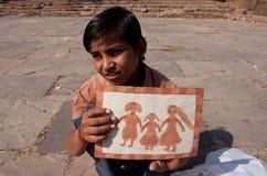 Pojken visar att hans föreställer av den lyckliga familjen Royaltyfri Fotografi
